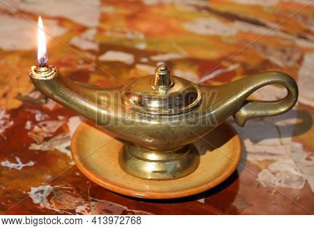 Ancient Oil Lamp With Burning Flame On A Marble Surface