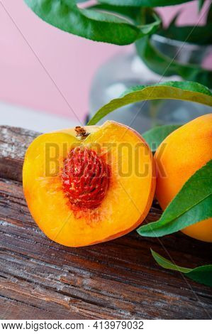 Peach In Halves With Bone. Peaches With Leaves On Wooden Board. Ripe Juicy Peaches. Fresh Organic Pe