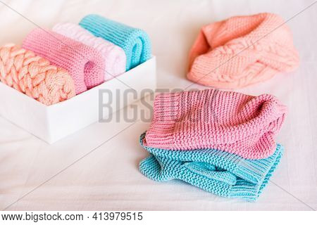 Organization And Order. Knitted Clothes Are In Disarray Next To A Box Of Neatly Folded Items
