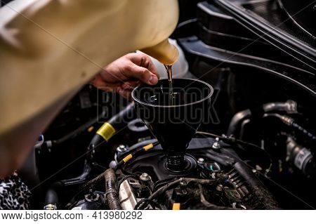 Close-up Of Mechanic Adding Oil With A Funnel