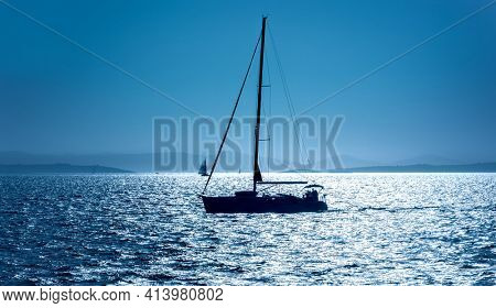 Sailboat in the sea in the evening sunlight over beautiful mountains background