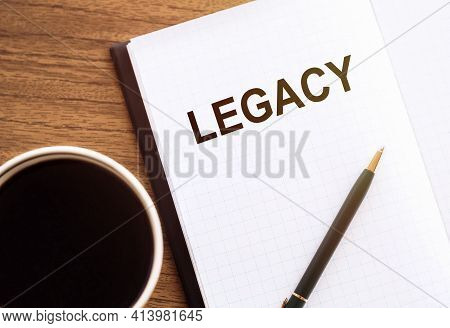 Legacy - Text On Notepad On Wooden Desk.