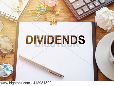 On A Wooden Table There Is An Office Sheet Of Paper With The Text Dividends. Business Workspace With