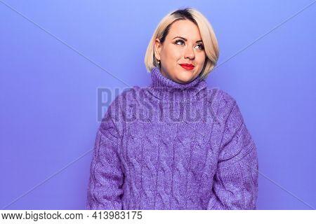Beautiful blonde plus size woman wearing casual turtleneck sweater over purple background smiling looking to the side and staring away thinking.