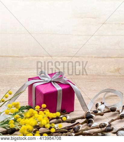 A Gift And A Mimosa Branch On A Wooden Background. Spring Flowers And A Gift Box. Yellow Mimosa And