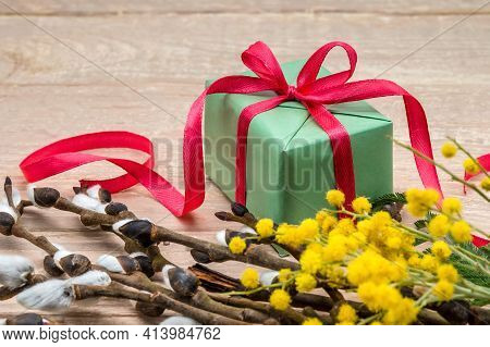 Yellow Mimosa And Fluffy Willow. Gift On A Wooden Background. Spring Flowers And Gift Box.