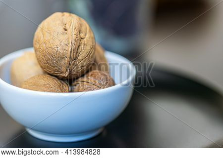 A Few Whole Walnuts In A Round-shaped Brown Shell Lie In A Small White Blue Platter On Black Plate O