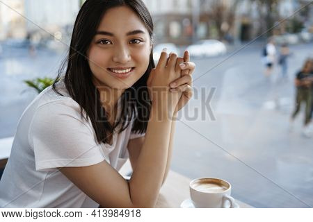Portrait Of Beautiful Natural Woman Drinking Coffee In Cafe Alone, Sitting Near Window, Smiling At C