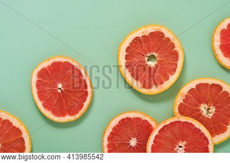 Grapefruit Citrus Pattern Composition. Grapefruit Slices With Juice Are Scattered Around On A Green