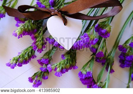 White Wooden Heart With Brown Silk Bow On Statice Purple Potpourri Flowers On White Background. Love