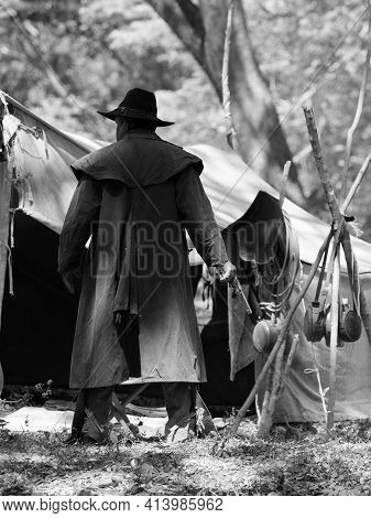 A Senior Cowboy Standing With A Gun To Guard The Safety Of The Camp In The Western Area