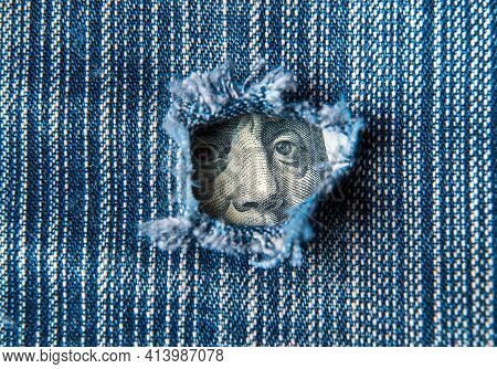 Hole In The Pocket Of Denim Pants From Which Dollars Are Visible. Symbolizes Crisis Or A Hole In The