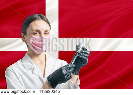 Girl Doctor Prepares Vaccination Against The Background Of The Denmark Flag. Vaccination Concept Den
