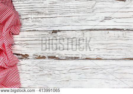Top View Of An Empty White Wooden Picnic Table And Crumpled Red And White Gingham Tablecloth At The