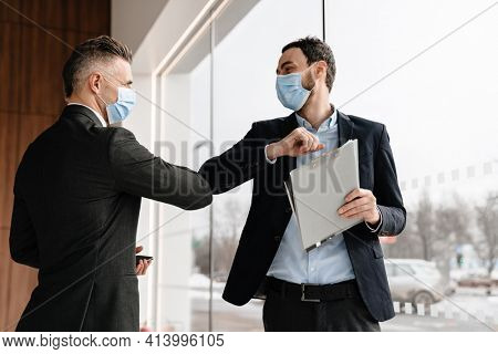 Pleased manager in face mask elbows bumping with customer indoors