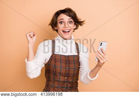Photo Portrait Of Amazed Schoolgirl In Spectacles Keeping Cellphone Gesturing Like Winner Isolated O