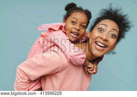 Joyful black mother and daughter with butterfly wings doing piggyback ride isolated over blue background