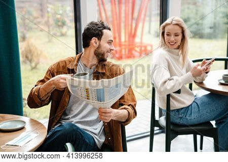 Smiling man and woman using cellphone and reading newspaper while talking in cafe