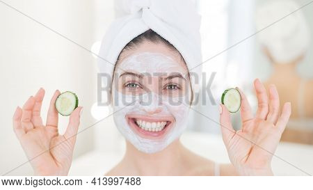 Cheerful Woman With A Towel On Her Hair And In A Clay Face Mask Fooling Around With Cucumbers In Her