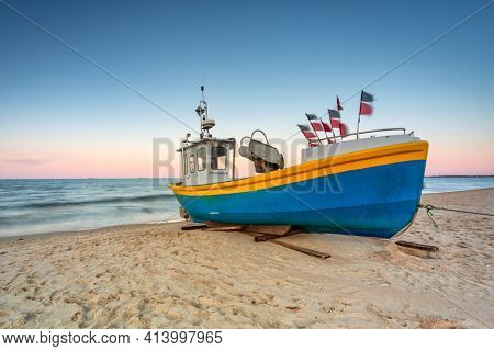 Amazing sunset with fishing boats at the beach of Baltic Sea in Sopot, Poland