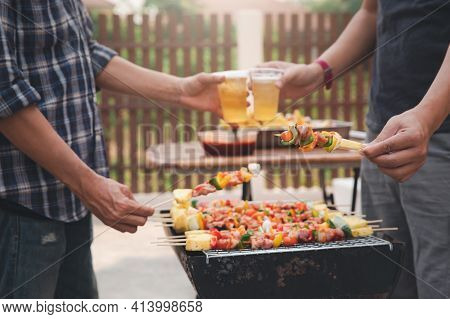 Young Men Cheers For A Drink At A Bbq Party Between Friends. Food, Drink, People And Family Time Con