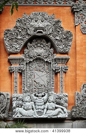 Detail of traditional asian Balinese carved relief with Barong on orange wall poster