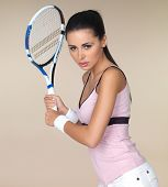 Attractive woman in sportswear playing tennis holding her racquet in both hands ready to play a backhand shot isolated on beige poster