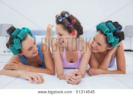 Laughing friends in hair rollers lying in bed and talking at sleepover