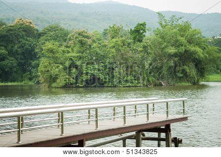 Metal Bridge Into The Pond