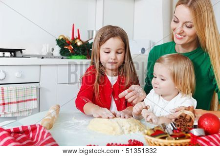 Two Adorable Girls With Her Mother Baking Christmas Cookies