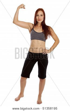 Young Woman Flexes Her Muscles In Fitness Clothing.