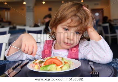 Sad little girl behind table in cafe poster