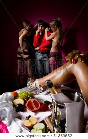 Guy having fun with woman decorated  by fruits and dancing stripteasers.