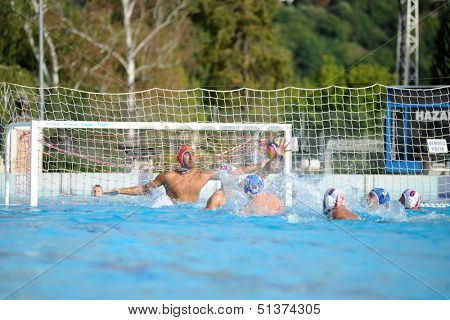 KAPOSVAR, HUNGARY - SEPTEMBER 15: Zoltan Szecsi (in red) in action at a Hungarian championship water-polo game between Kaposvar (white) and Honved (blue) on September 15, 2013 in Kaposvar, Hungary