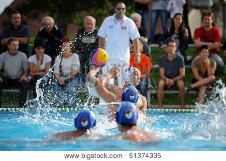KAPOSVAR, HUNGARY - SEPTEMBER 15: Norbert Juhasz-Szelei (white) in action at a Hungarian championship waterpolo game between Kaposvar (white) vs Honved (blue) on September 15 2013 in Kaposvar, Hungary