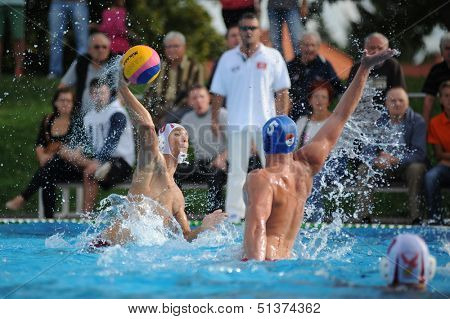 KAPOSVAR, HUNGARY - SEPTEMBER 15: Romeo Kutasi (with ball) in action at a Hungarian championship water-polo game between Kaposvar (white) and Honved (blue) on September 15, 2013 in Kaposvar, Hungary