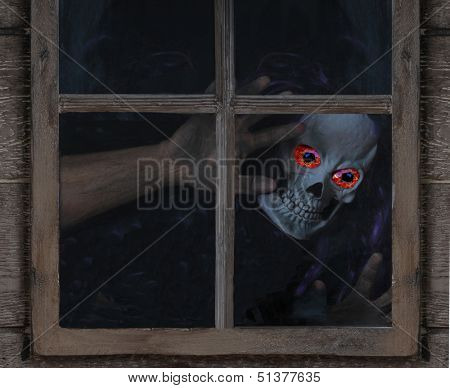 Scary Halloween ghoul with glowing eyes looking inside rustic window..