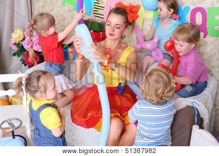 poster of Five happy kids and facilitator make dogs of long balloons at children party. Inscription Happy Birthday on wall.