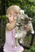 Small happy girl embraces by hands kitten poster