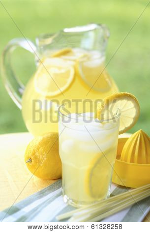 summer still life of lemonade in glass with garnish and full pitcher in background on wood table