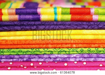 Textile background.  Macro of folded cotton fabrics in bright colors. Swatches in coordinated colors for quilting, crafts, or home decor sewing projects.