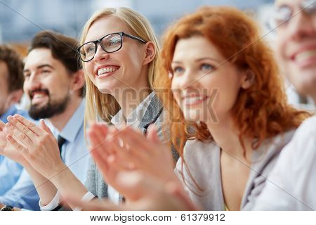Photo of happy business people applauding at conference, focus on smiling blonde poster