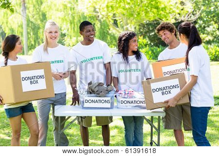 Group of male and female volunteers with donation boxes in park