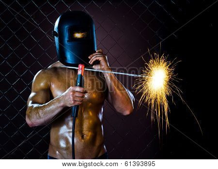 poster of the beauty muscular worker welder man weld electric arc-weld on netting fence background
