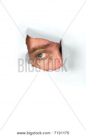 Man Peeking Through Torn Paper