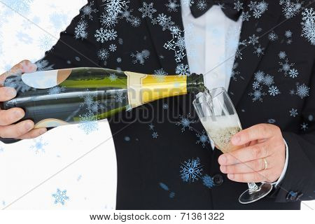 Welldressed man pouring champagne against snow falling