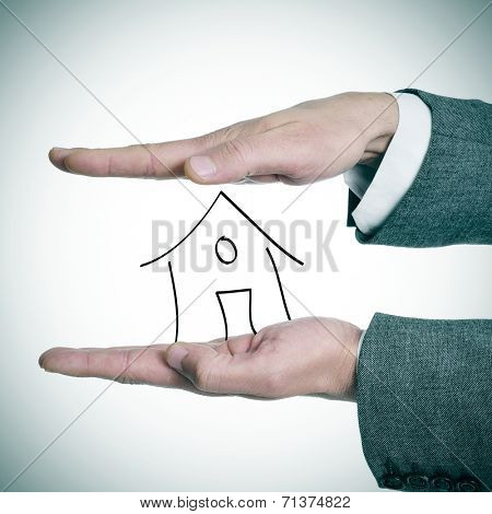 a businessman holding a drawing of a house in his hands