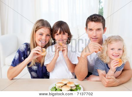 Smiling Family Eating Burgers In The Living Room