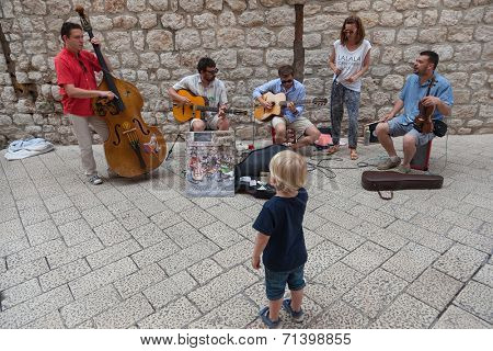 DUBROVNIK, CROATIA - MAY 26, 2014: Little boy watching band performing on Stradun.  Stradun is 300 meters long main pedestrian street in Dubrovnik.