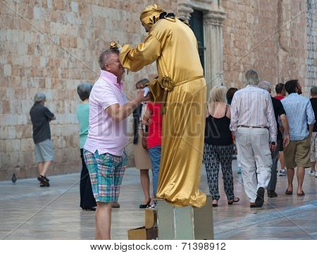 DUBROVNIK, CROATIA - MAY 26, 2014: Tourist shaking hand with local street performer in golden costume on Stradun. Stradun is 300 meters long main pedestrian street in Dubrovnik.